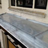 Zinken dakbedekking van erker vervangen.
